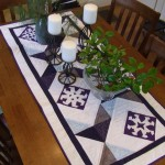 Half square triangles winter table runner with snowflake appliqué